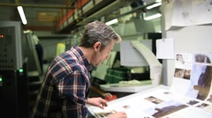 Man in printing house controling sample before edition Stock Footage