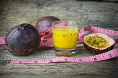 Passion fruits with glass of passion fruit juices with measuring tape on wood - stock photo