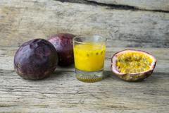 Passion fruits with glass of passion fruit juices on wooden - stock photo