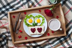 Breakfast in bed with heart-shaped eggs, toasts, jam, coffee, rose and petals Stock Photos