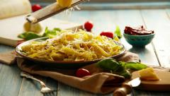 Cheese grating Just cooked Pappardelle italian cuisine dish on the rustic table Stock Footage
