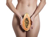 Nude woman with a papaya Stock Photos
