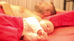 Baby sleeps peacefully his father wake up Stock Footage