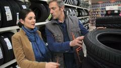 Customer in car shop choosing new tires Stock Footage