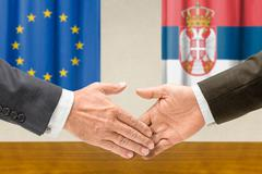 Representatives of the EU and Serbia shake hands - stock photo