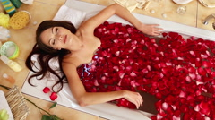 Young woman is relaxing with rose petals  bath in spa salon Stock Footage