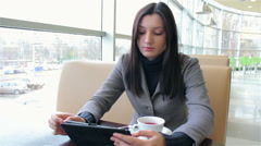 business woman drinking coffee and working on a tablet - stock footage