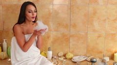 Woman taking a bath and blowing on foam in her bathroom Stock Footage