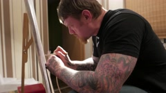Tattooed man with airbrush in his hands. Stock Footage