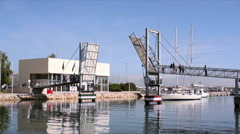 Yacht sailboat passes under moveable pedestrian bridge, Lagos, Portugal Stock Footage