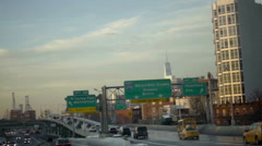 Cars driving on FDR Drive at sunset with Freedom Tower skyscraper and signs NYC Stock Footage