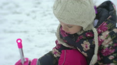 Kid is Digging a Snow With Pink Shovel Girl is Playing Outdoors Sitting on Her Stock Footage