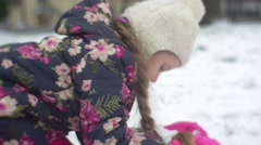 Kid Sits to a Ground Grabs the Heap of Snow Winter Little Girl is Raising up Stock Footage