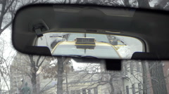 driver pov moving car with taxi cab in rearview mirror in cold winter NYC - stock footage