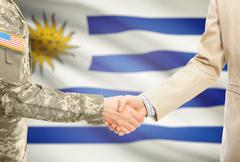 American soldier in uniform and civil man in suit shaking hands with national Stock Photos