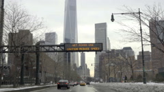Wet roads use caution reduce speed sign Freedom Tower view West Side Highway NYC Stock Footage
