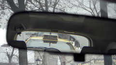 Zooming out from taxi in rearview mirror from driver pov bare winter trees NYC Stock Footage