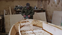 A carpenter polishes details wooden boat at the shipyard Stock Footage