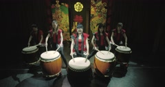 A group of Japanese Taiko drummers girls performs on stage,a dark background Stock Footage