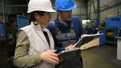 Metal worker in workshop checking production with engineer - stock footage