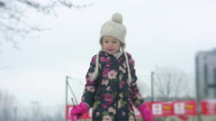 Little Girl Slides Downhill by Snow Holding a Branch Happy Girl in Winter at Stock Footage
