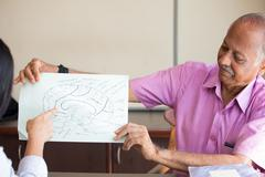 Closeup portrait, elderly in pink shirt lecturer explaining anatomy to health - stock photo