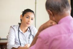 Closeup portrait, patient talking serious conversation to healthcare professi Stock Photos