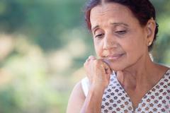 Closeup portrait, morose elderly lady, downcast gloomy, resting face on hand, - stock photo
