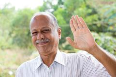 Closeup portrait, amiable old man waving hi or farewell, isolated outdoors ba Stock Photos