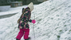 Little Girl is Climbing up the Hill With a Branch Stick Walking by Snow Stock Footage