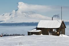 Wooden house volcanologists on background erupting volcano Kuvituskuvat
