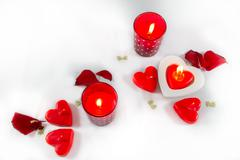 Valentines Day hearts,  candles and rose petals on white background- top-view - stock photo