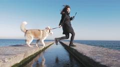 Young girl training siberian husky dog on sea pier, 4k - stock footage