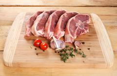 Raw meat lamb entrecote on bone on a wooden board Stock Photos