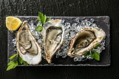 Oysters served on stone plate with ice drift - stock photo