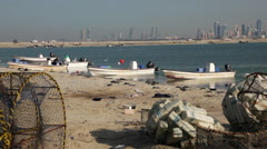 Fishermen boats beside the sea in Bahrain. Manama City skyline in the background Stock Footage