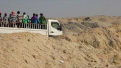 Transport of people in a pick-up on the desert Stock Footage