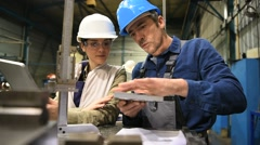 Engineer manager checking conformity with metal worker Stock Footage