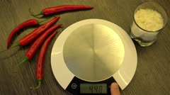 Weigh mandarins on kitchen small electronic scales Stock Footage