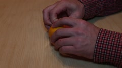 man cleans tangerine - stock footage