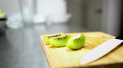 Sliced Kiwi on Cutting Board with Ceramic White Knife - 4K Resolution Stock Footage