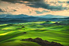 Stock Photo of Tuscany spring, rolling hills on sunset. Rural landscape. Green fields and fa