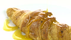 Pouring honey on croissant, rotating, close-up, slow - stock footage