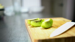 Sliced Kiwi on Cutting Board with Ceramic White Knife 60 fps Stock Footage