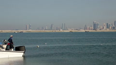 Fishermen boat in the Bahraini sea. Manama City skyline in the background Stock Footage
