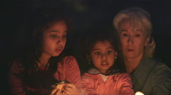 Grandma helping two little girls roast marshmallows over open fire. Stock Footage