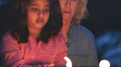 cure little girl roasting marshmallows with her grandmother - stock footage