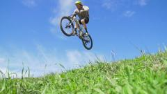 Super Slow Motion Extreme Man Moutain Biking Down Grassy Hill In Air Stock Footage
