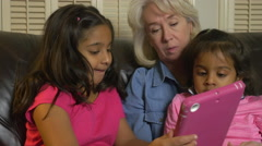 Two young sisters and their grandmother with tablet pc - stock footage