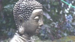 Buddhist sculpture stands under rain on a background of green spruce branches Stock Footage